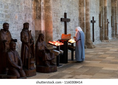 Vezelay, France - July 29, 2018: Church Interior with nun rearranging the candles of the romanesque abbey and church of Vezelay in Yonne, France.