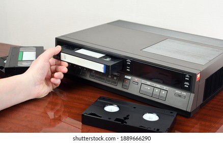 VHS videocassette is put into the video recorder to watch the video, another video cassette is on the video-tape recorder