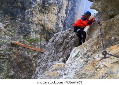 "Via ferrata climber traversing towards wooden on ""Brigata Tridentina"" route, Sella massif, Dolomite Alps, Italy"