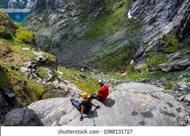Via ferrata climbers sitting and resting on a cliff. Himmestigen via ferrata , way to Trolltunga , Norway, Europe