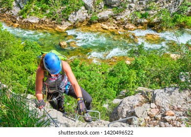 Via ferrata in Croatia, Cikola Canyon. Young woman climbing a medium difficulty klettersteig, with turquoise colors of Cikola river in the background.