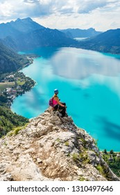 Via ferrata female climber enjoying the views over lake Attersee, Austria, with blue waters, in a bright, hot, Summer day. Perfect Summer destination for rock and water activities.