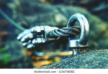 Via ferrata steel rope on a rock detail. Steel chrome anchores in rock hold steel rope