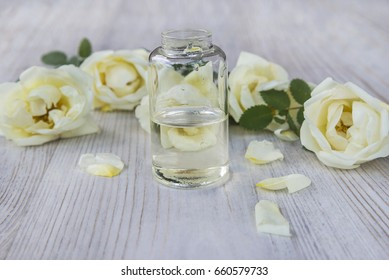 vial with tea roses essential oil on light wooden background