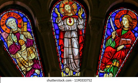 Viana do Castelo, Portugal - August 4, 2014: Stained glass window depicting Saint Peter, Jesus Christ and Saint John the Evangelist in the church of Viana do Castelo, Portugal.