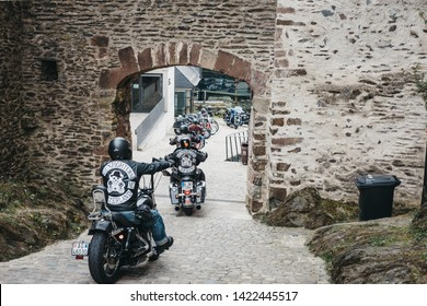 Vianden, Luxembourg - May 18, 2019: Gunfighters bikers riding through a gate inside Vianden Castle, Luxembourg, one of the largest and finest feudal residences of the Roman and Gothic eras in Europe.