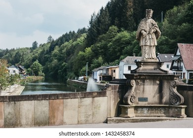 Vianden, Luxembourg - May 18, 2019: Statue of Saint John of Nepomuk on a bridge over the river Our in Vianden, a town in Luxembourgs Ardennes region known for the centuries-old hilltop Vianden Castle.