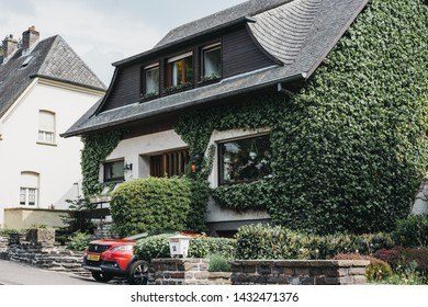 Vianden, Luxembourg - May 18, 2019: Facade of a typical Luxembourgish house covered in green ivy in Vianden, town in Luxembourg's Ardennes region known for the centuries-old hilltop Vianden Castle.