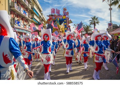 VIAREGGIO - FEB 26: people dancing around the allegorical float on the path of Viareggio at the Carnival of Viareggio February 26, 2017 in Viareggio, Italy.