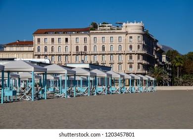 Viareggio, Italy - 09/29/2018: Beach Cabins with the Grand Hotel Principe Di Piemonte in the Background