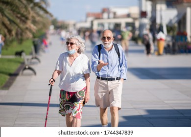 VIAREGGIO,ITALY-MAY,27,2020: old couple  walk wearing protective masks in the promenade  the first weeked of free moving  after quarantine was declared in march