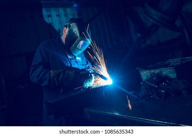 A vibrant action shot of a skilled working metal welder in action, welding metal. Photographed with a slow shutter speed and spark trails. Orange and teal.