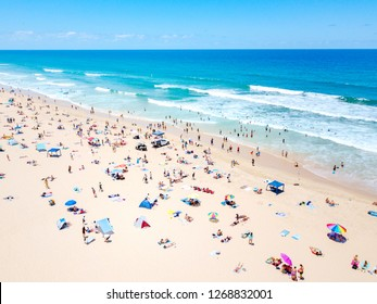 A vibrant aerial view of people at the beach on a busy summer day in Surfers Paradise on the Gold Coast in Queensland, Australia with turquoise water