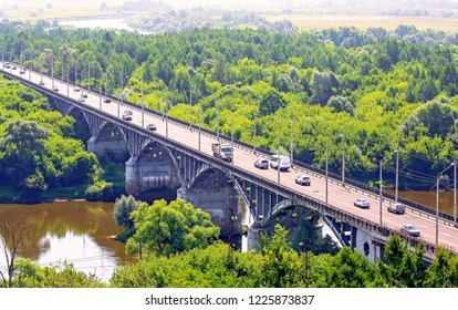 Vibrant aerial view of a river arch automobile stone bridge with moving cars near Vladimir in summer