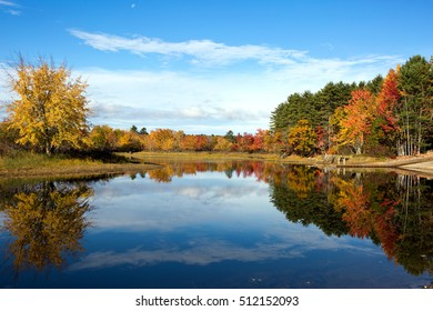 Vibrant autumn leaves and colors of fall tree foliage reflect on the waters of Lake Sabago, Maine in October.