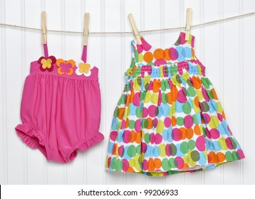 Vibrant Baby Dress and Bathing Suit on a Clothesline