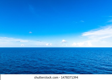Vibrant blue color in the open sea. The water has a darker tonality than the sky creating a beautiful contrast