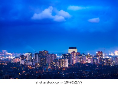 Vibrant city lit up at night beneath cloudy weather. Background with space for text.