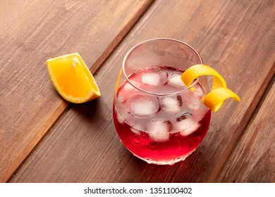 A vibrant cocktail with campari and an orange curl garnish, with ice cubes and an orange slice, on a dark rustic wooden background, with a place for text