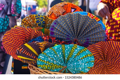 Vibrant colored fans made from West African fabric for sale at a local market