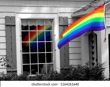 Vibrant colorful pride rainbow flag flying outside a house, colorfully reflected in the window: background in black and white- symbol of lgbt support and unity as an ally