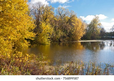 vibrant colors of autumn along wooded banks of black dog lake at minnesota valley national wildlife refuge in eagan minnesota