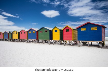 Vibrant Coloured wooden beach huts on the beach at Muizenberg, Cape Town