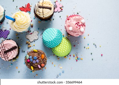 Vibrant cupcakes on blue background, party food concept, overhead