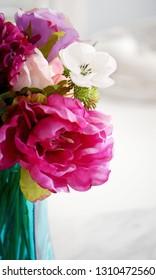 Vibrant fabric flowers in aqua vase.  Vertical format, natural light.