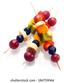 Vibrant fresh fruit kebabs for a healthy snack with assorted grapes, strawberries, blueberries, banana, kiwifruit and orange on wooden skewers on white