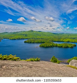 Vibrant green and blue view of mountains, lakes, and islands from Mt. Megunticook in Camden, Maine, New England, USA.  Foreground rock has room for text.