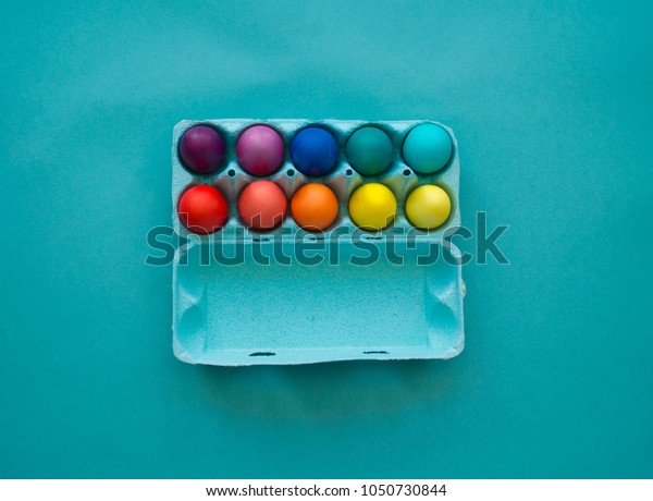 Vibrant hand dyed colorful Easter eggs in a cardboard egg box viewed from above on a blue background with copy space for your greeting