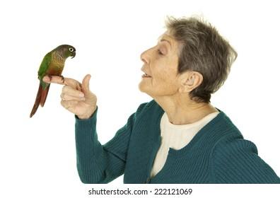 Vibrant Happy Senior Woman on a White Background Talking to her pet bird