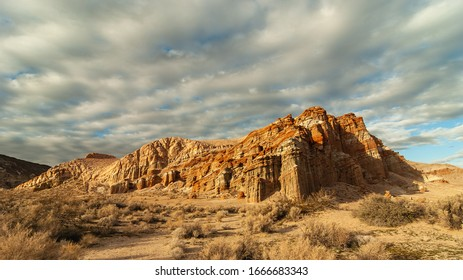 Vibrant image of the Red Cliffs in Red Rock Canyon State Park in California against a morning sky with clouds.