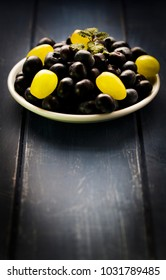 Vibrant image of two fruits; blueberries and grapes on wooden base with green leaf for decoration