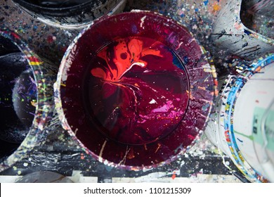A vibrant large pot of maroon and red acrylic block printing and screen printing paint in a bucket in an industrial creative art studio setting.