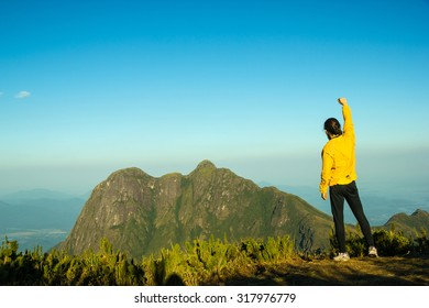 Vibrant Man celebrating success on top of a mountain