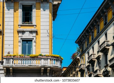 Vibrant Mediterranean colorful yellow building facade and balcony in Milan, Lombardy, Italy.