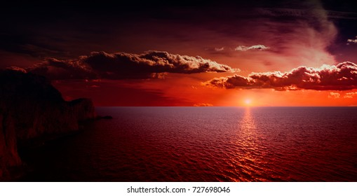 vibrant orange red sea sunset featuring a cloudy sky and a rocky cape