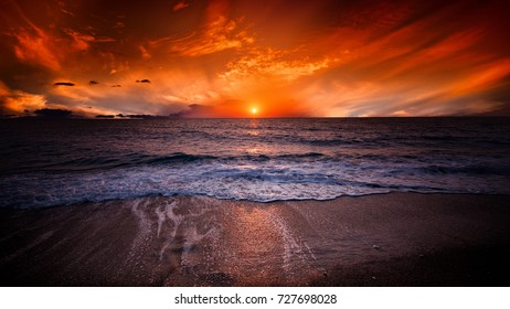 vibrant orange sea sunset, featuring bright sun low on the  horizon and a cloudy sky