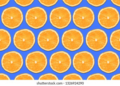 Vibrant orange slices isolated on blue background. Fruit section design texture. Vitamin diet pattern.