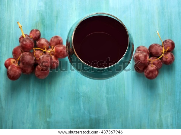 A vibrant photo of a glass of red wine with bunches of grapes, shot from above on a turquoise blue wooden background texture, with copyspace