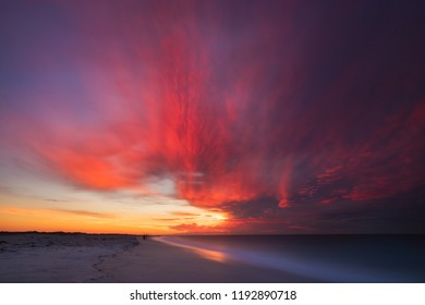Vibrant pink and orange clouds streak across the sky as the sun rises above a coastline - copy space. Long Island New York