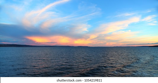 Vibrant pink, orange, and yellow sunset with soft, wispy clouds against blue sky over Puget Sound