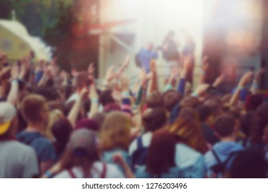Vibrant pop music concert background.Big group of happy young people partying on musical festival in night club.Colorful abstract back ground for nightclub party poster.Fans hands and bright lights