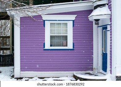 A vibrant purple exterior wall of a vintage building with a small double hung window. The trim around the window is white. There's a blue exterior door with a step covered in fresh white snow.