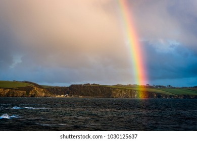 A vibrant rainbow arches across St Austell Bay  and the small coastal town of Polkerris in Cornwall