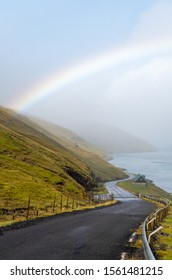 A vibrant rainbow perfectly formed above a winding road leading into the distant mountainside coastline. Taken in the Faroe Islands.