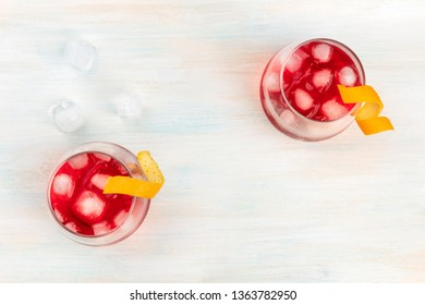 Vibrant red cocktails with campari and orange twist garnishes, with ice cubes, shot from the top forming a frame for copy space