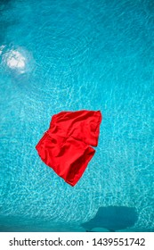 A vibrant red pair of swimming shorts floating on a pool